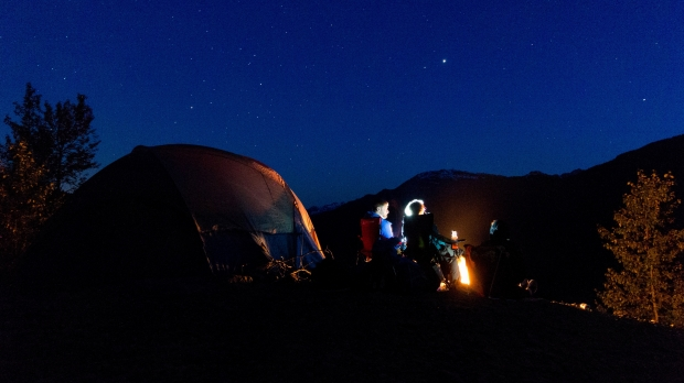 Two people sit by a tent on a camping trip