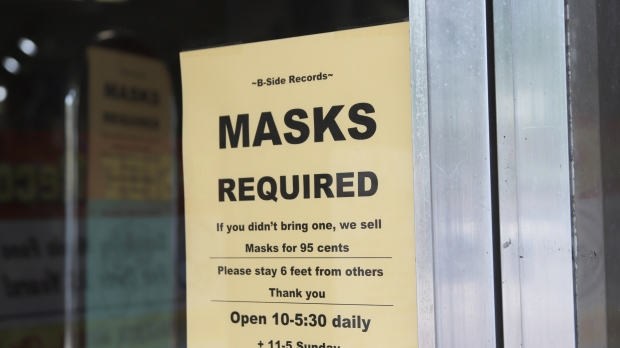 A sign outside B-Side Records in Madison explains the store's mask policy