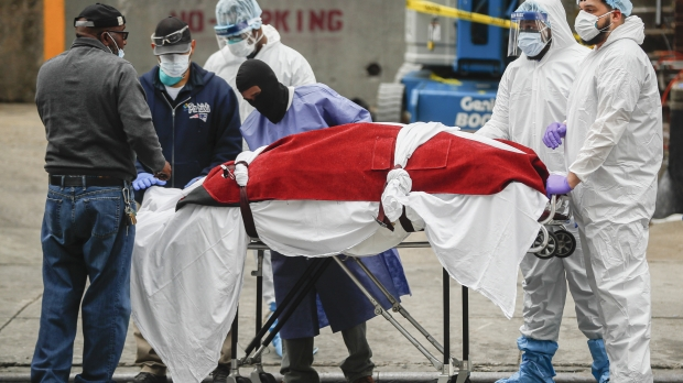A body wrapped in plastic is handled by medical workers in Brooklyn