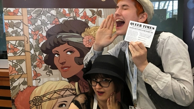 A photo of the two founders of Margins publishing striking fun poses in front of a printed comic graphic backdrop from one of their published works.