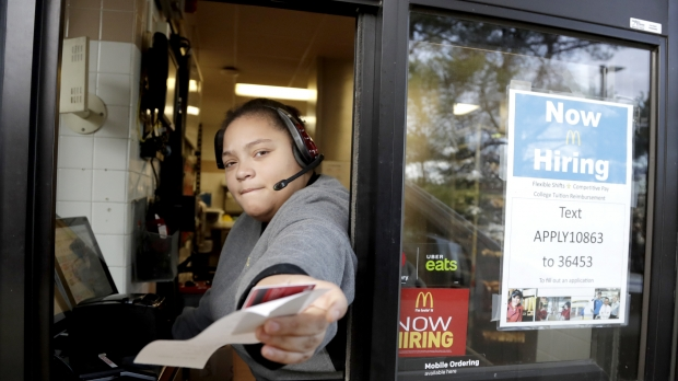 A cashier returns a credit card and a receipt at a McDonald's window.