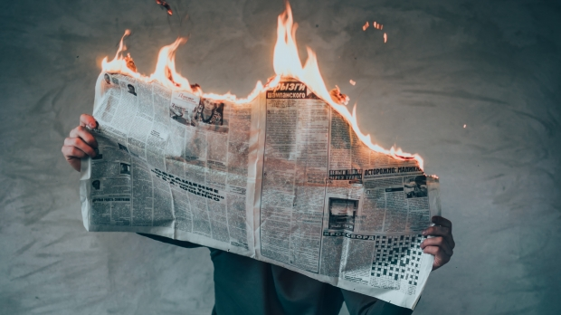 Man reading burning newspaper