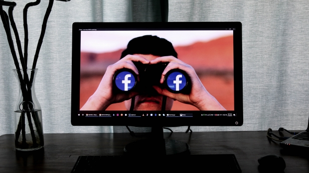 A man on a TV screen holding binoculars with Facebook logo in eyepieces
