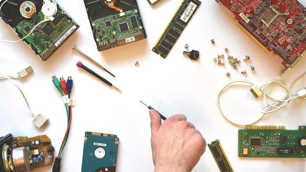 A variety of technology parts are taken apart on the counter.
