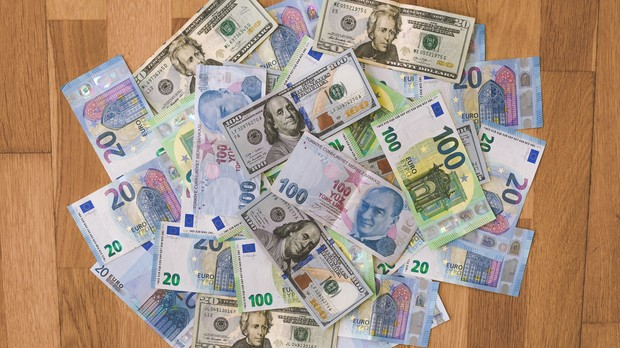 U.S. dollars, European euros, and Turkish lira bills mixed together in a pile on a wooden floor