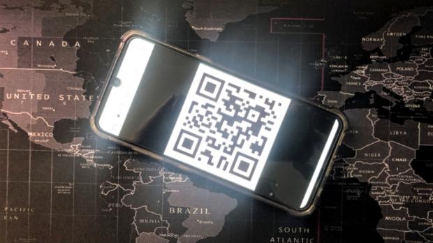A phone shows a QR code for a vaccine passport