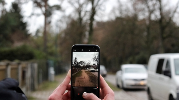 A person holds up their smartphone to capture a photo.