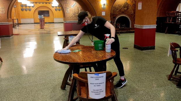 A worker cleans a table at UW-Madison
