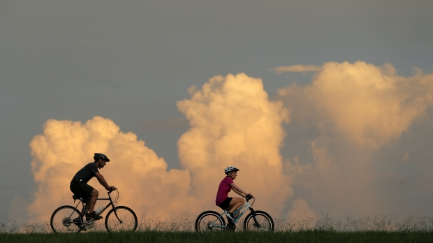 People ride bikes with cumulus clouds in the background.