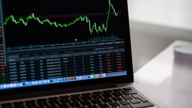 A laptop screen shows the stock market graph.