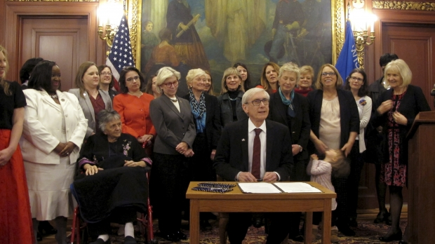 Wisconsin Gov. Tony Evers is surrounded by women in state government after he signs a proclamation recognizing the 100th anniversary of Wisconsin being the first state to ratify the 19th Amendment