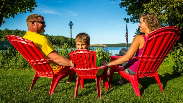 A family sitting in red chairs on a green lawn
