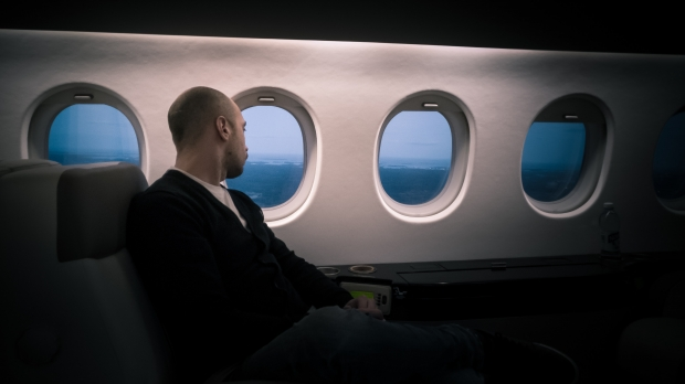man on airplane sitting near window