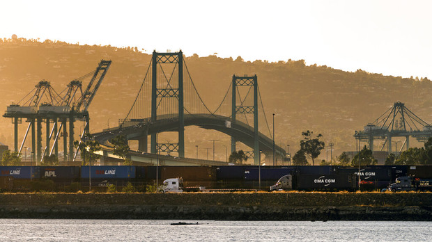 Trucks line up next to containers being shipped by rail line in Terminal Island in Los Angeles.