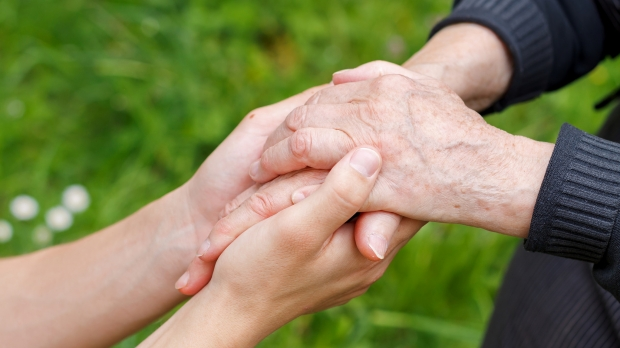 Two people of different ages holding hands