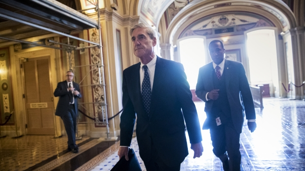 Robert Mueller walking through the Capitol with two men and the sun behind him