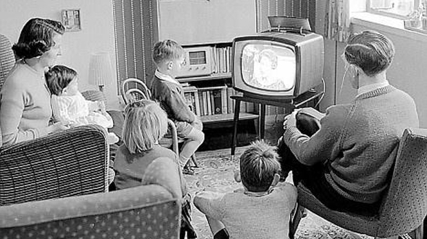 a 1950s family gathers around the TV