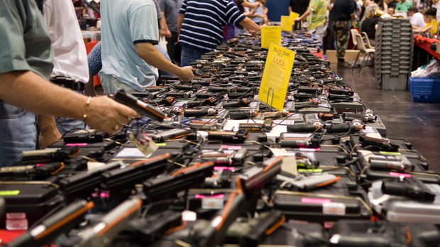 many guns displayed on a table at gun show