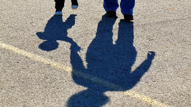Shadow of two kids on asphalt