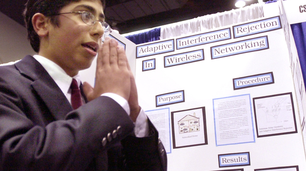 Student stands in front of board at Science Fair