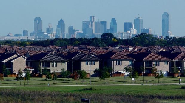 row of similar suburban houses, city skyline in background