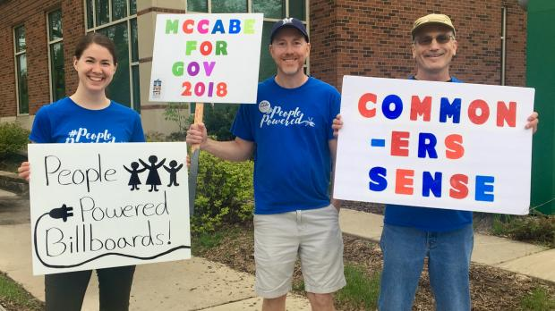 McCabe supporters hold signs outside a McCabe campaign event