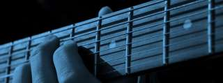 Blue-tinted photo of fingers on a guitar fretboard