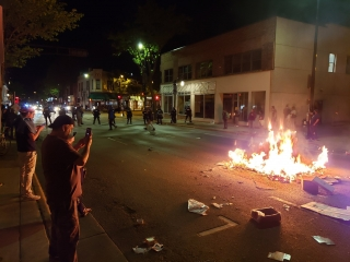 A crowd backedoff to let Madison firefighters put out the trash fire in the middle of Johnson Street in downtown Madison on Saturday night.