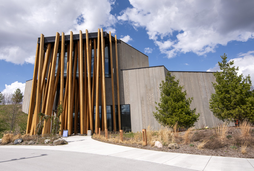 Large wooden beams are the front facade of a modern museum building.