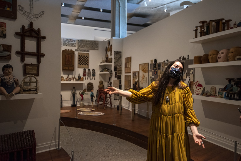 A woman gestures as she walks through an art display.