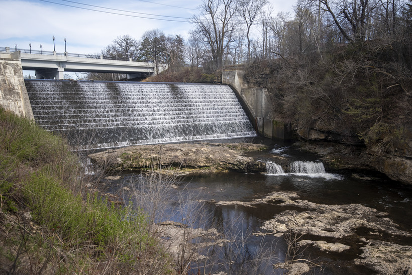 River water flows from under a bridge and down a slope