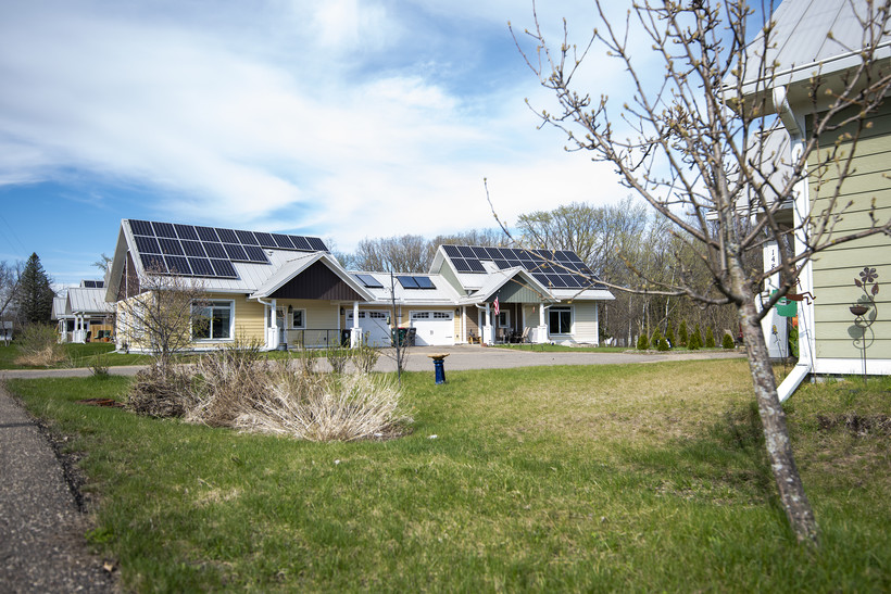 The roofs of two small homes are covered in solar panels.