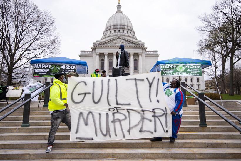 """A banner reads """"guilty of murder."""""""