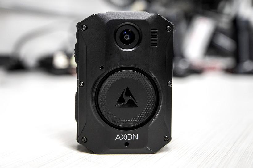A rectangular black device has a camera lens facing outward.
