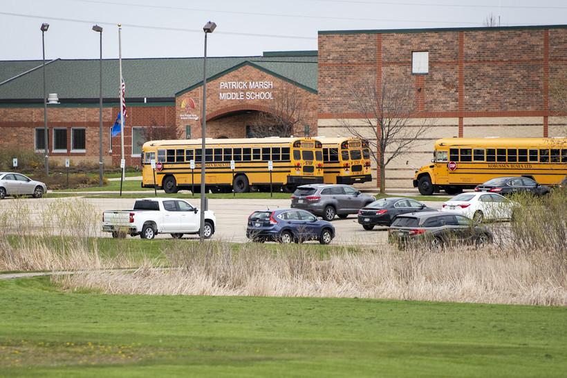 Three yellow school buses are parked in front of a brick school building.
