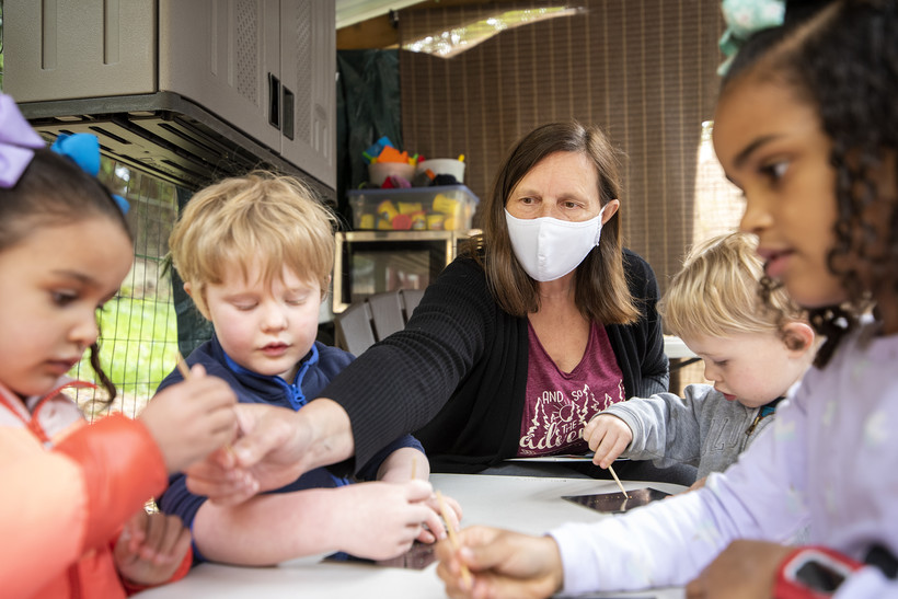 Four children sit at a small table. A woman in a face mask hands out craft tools.