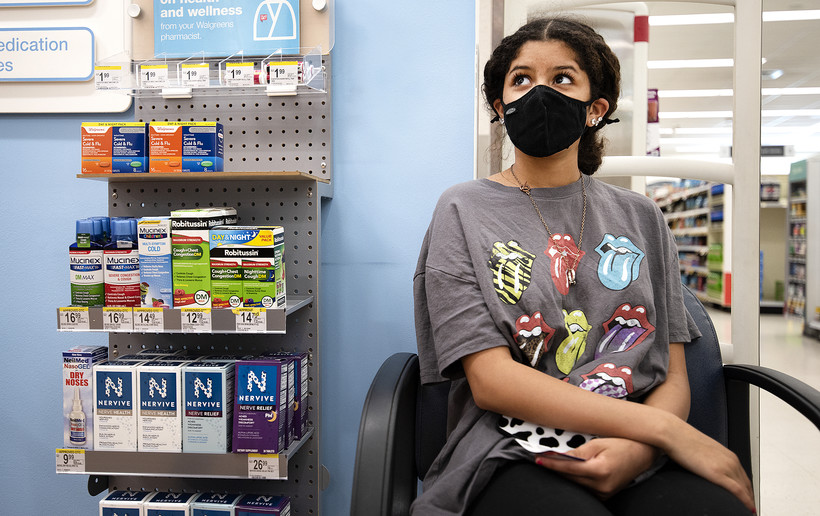 A girl in a t-shirt and face mask sits near products in a pharmacy.