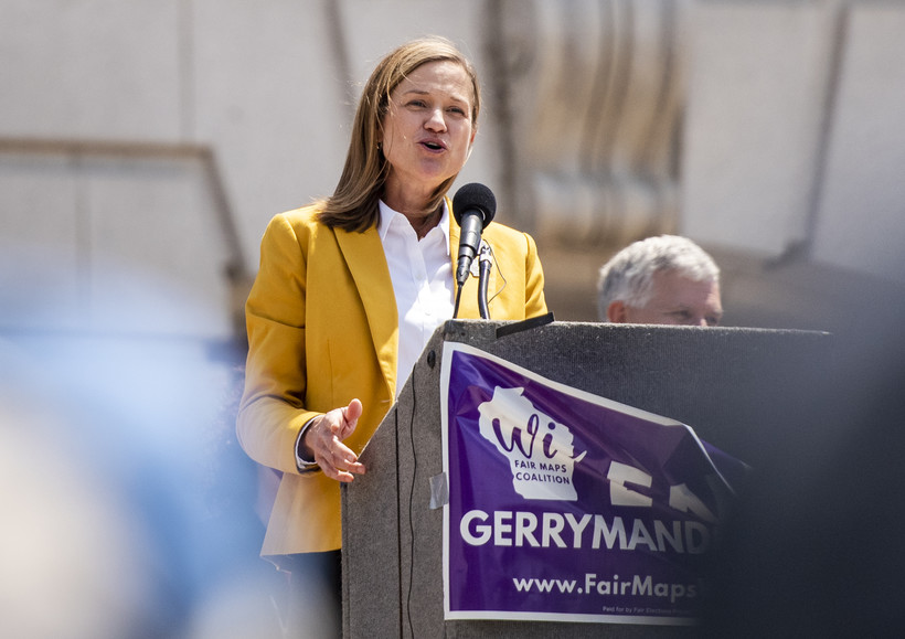 A woman in a yellow coat speaks at a podium.