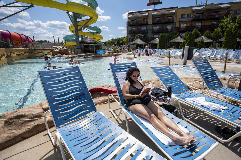 A woman sits in a chair near a pool as she reads a book in her swim suit.