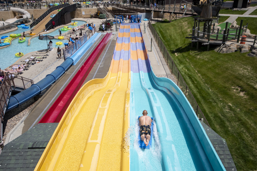 A man slides down a yellow and blue water slide.