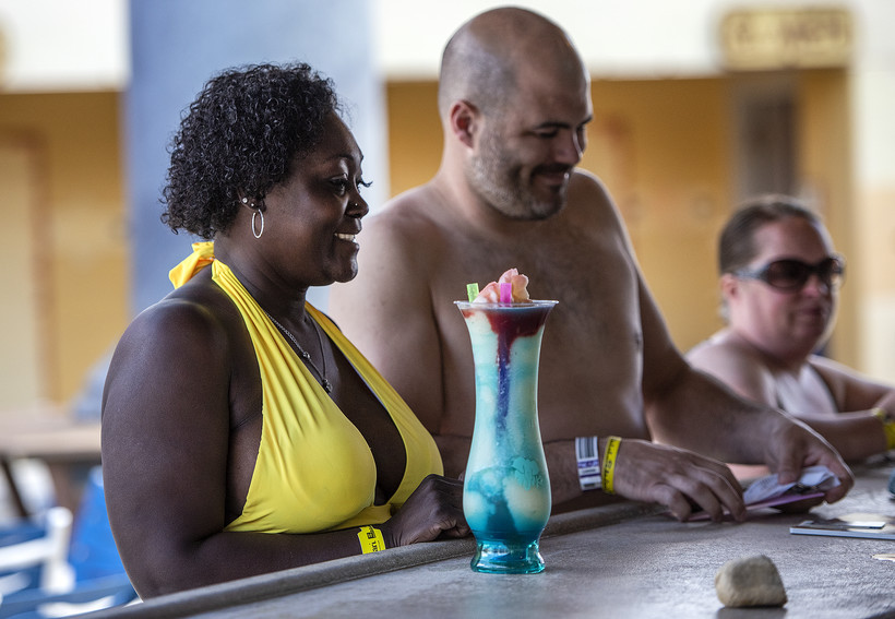 A woman and a man stand near a colorful drink at a bar.