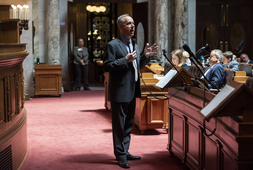 Assembly Speaker Robin Vos stands on red carpet as he speaks at the front of the chamber.