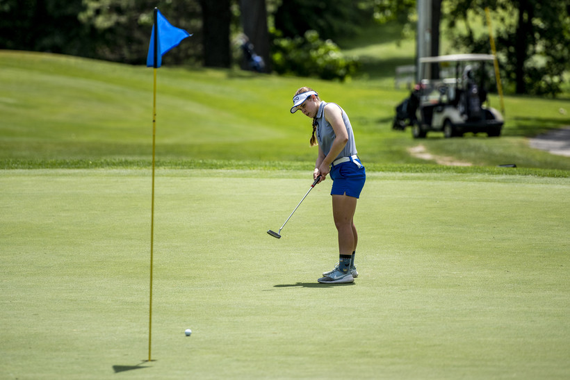 A girl watches as her ball rolls toward a hole marked with a blue flag.
