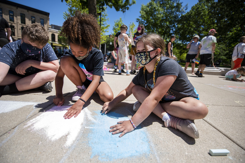 Two children color with chalk outside.