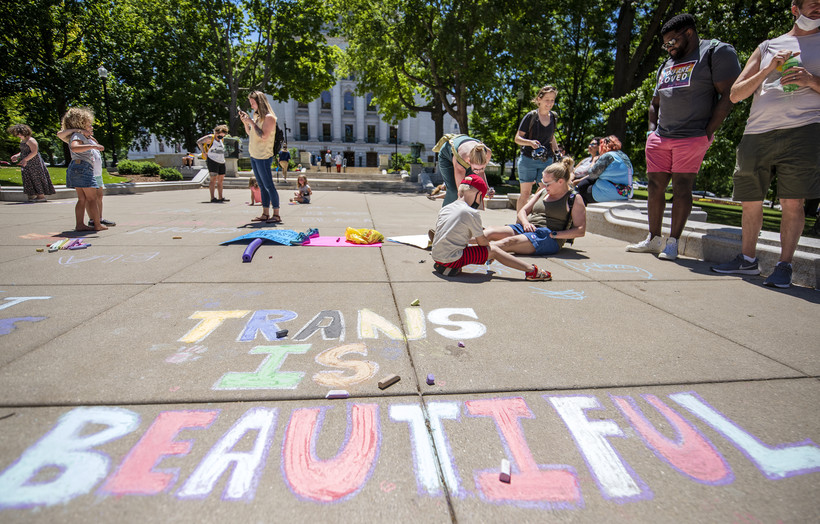 """The words """"Trans is beautiful"""" are written on a sidewalk."""