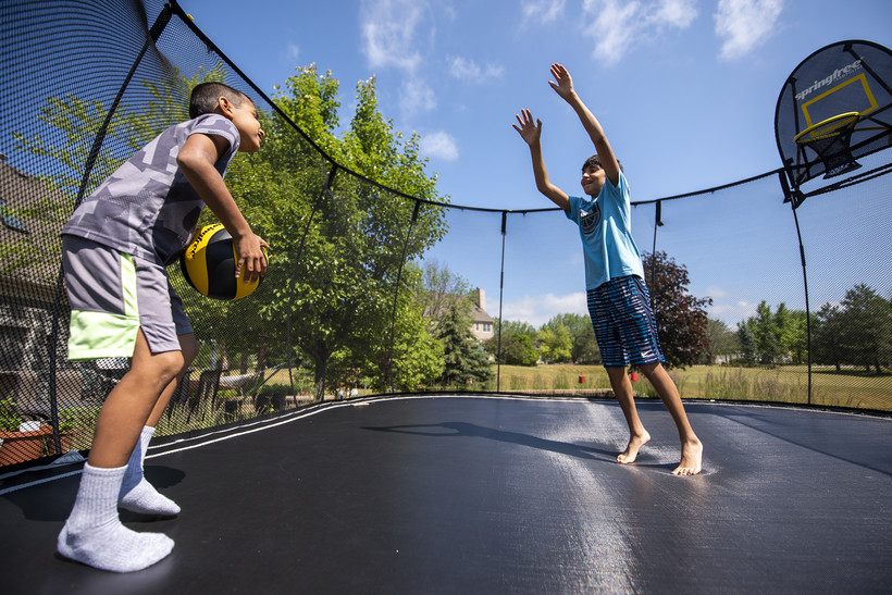 Two children play on a trampoline on a sunny day.