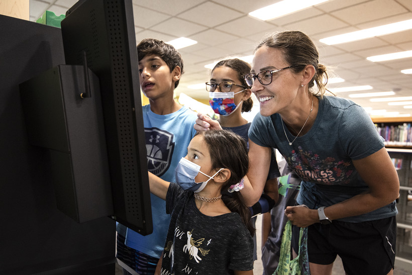 A family gathers around a screen to check out library books.