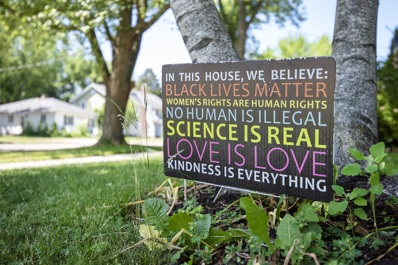 """A sign says """"In this house, we believe: Black Lives Matter, women's rights are human rights, no human is illegal, science is real, love is love, kindness is everything"""""""