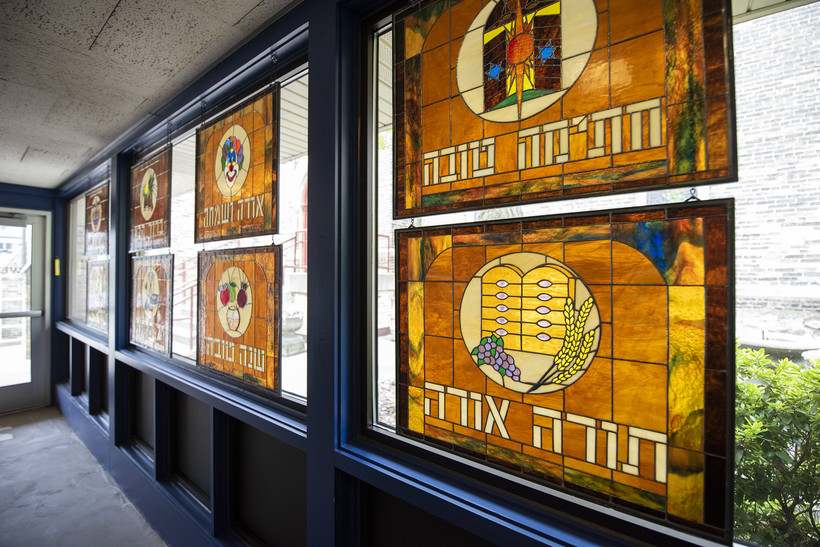 Amber colored stained glass depicting different Jewish holidays are displayed on a window.
