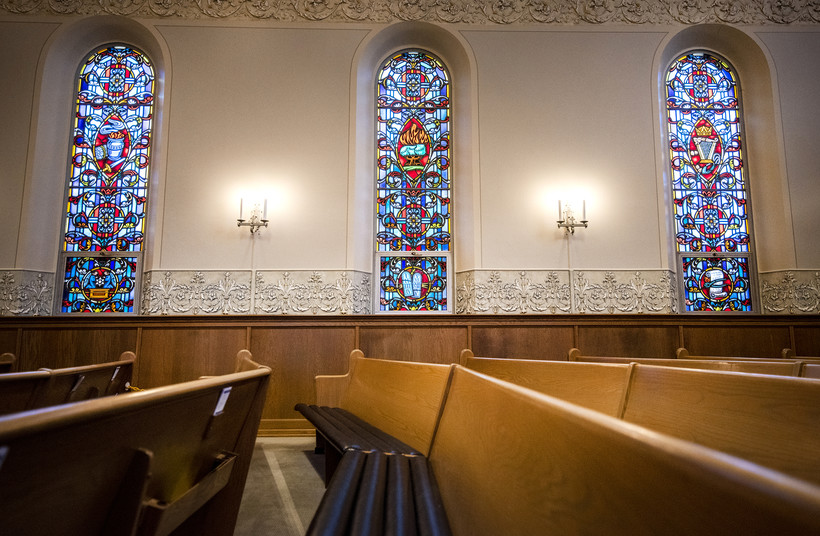 Three tall and narrow windows featuring vibrant stained glass are seen behind church pews.